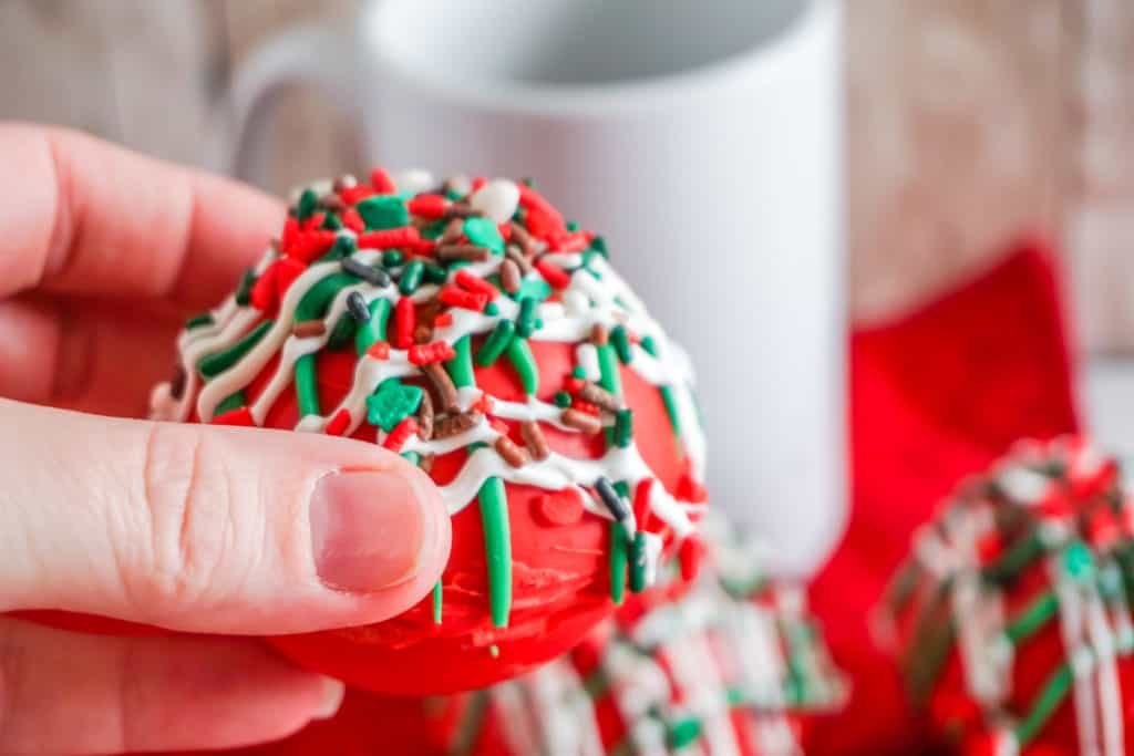 These are the most festive hot cocoa bombs you can make at home. They have hot chooclate, marshmallows, and nougat to create a delightful explosion of flavor and color.